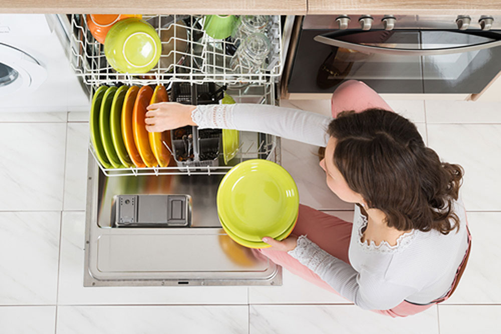 Woman loading a dishwasher