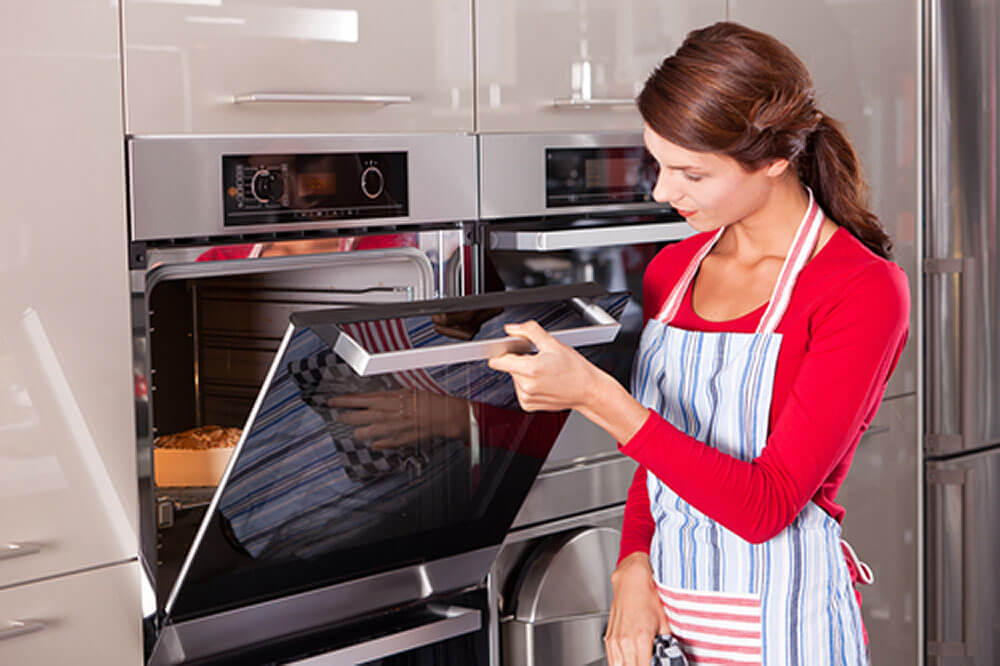 Woman cooking in electric oven
