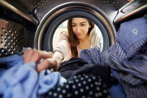 Woman taking out clothes from the tumble dryer