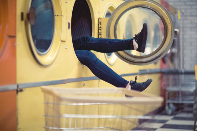 A person's legs sticking out of a large washing machine