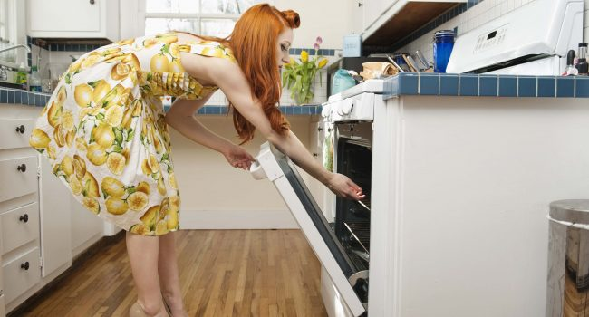 woman reaching in an oven