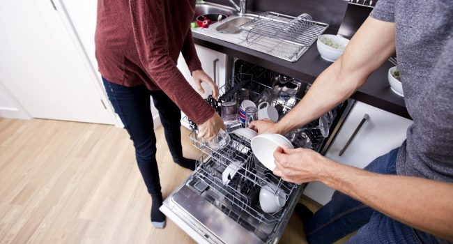 man and woman loading a dishwasher